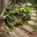 pad van oude dekstenen naar de kruidenheuvel en links de moestuin